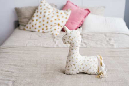 Unicorn soft toy on the bed on the background of multi-colored pillows Stock Photo