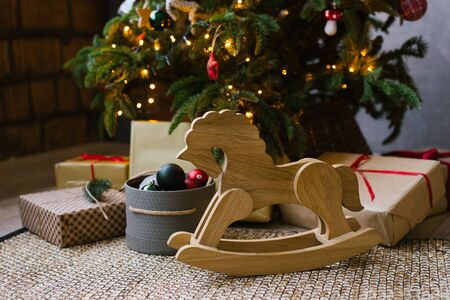 A wooden rocking horse for children stands next to Christmas gifts under a Christmas tree with lights Stock Photo