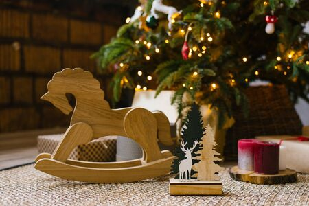 A wooden rocking horse for children stands next to Christmas gifts under a Christmas tree with lights Banco de Imagens