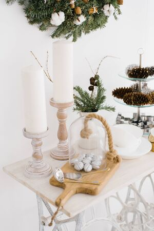 Christmas decor on a white table. Candles, silver walnuts on a chopping Board Stock Photo