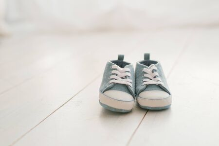 Childrens shoes, denim sneakers for baby on a light wooden background. Copy space Zdjęcie Seryjne