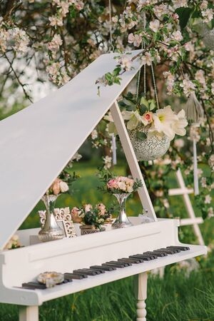 Decorative piano with decor in a blossoming Apple orchard at a wedding