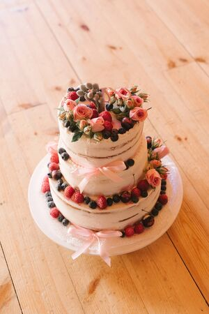 Beautiful wedding cake with fresh berries on wooden background