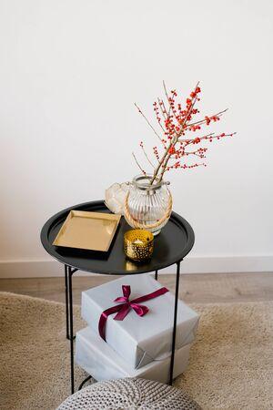 Una mesa de café con una bandeja de oro, ramas con frutos rojos en un jarrón de vidrio y cajas de regalo con cintas y un lazo. Foto de archivo