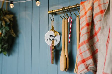 Wooden kitchen spoon and toy with happy Christmas inscription, red grey towel on hooks in Scandinavian style kitchen 免版税图像