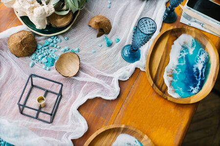 Marine decor on a festive wooden table. Plate with epoxy resin in the form of sea waves, coconut and blue glasses