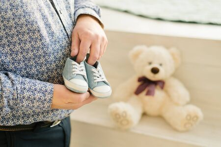 The future father holds in his hands blue sneakers for the baby, a pleasant and tremulous expectation of the future child of the son.