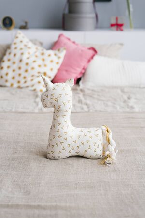 Soft unicorn toy on the bed with pillows in the bedroom bedding colors Imagens