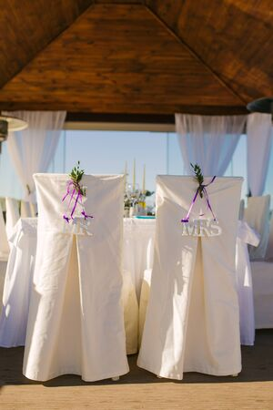 """Wedding chairs in white covers of the bride and groom with the words """"mr"""" and """" mrs """" in the gazebo outdoors"""