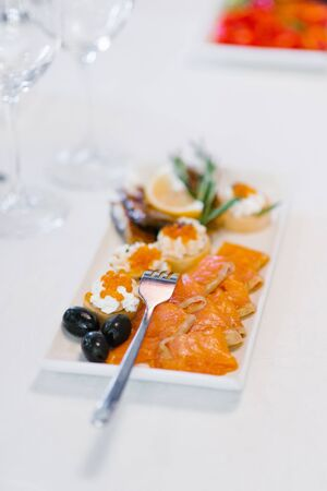 Salmon with appetizers on a white plate and a fork on the table