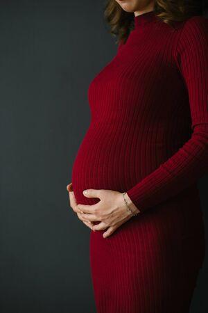 Una mujer embarazada con un vestido de Borgoña de punto tiene sus manos sobre su estómago. Embarazo hermoso y feliz. Esperando al feto