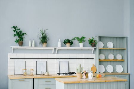The interior of the kitchen in Scandinavian style in white and mint colors.