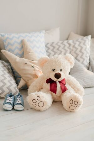 Baby shoes for newborn. Blue sneakers for the boy in the nursery. Soft toy bear