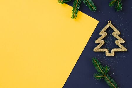 Christmas composition. Postcard background for desktop. Stylish decor concept, white sparkling Christmas toys and fir branches on dark blue and yellow multi-colored background. Flat, top view, copy space.