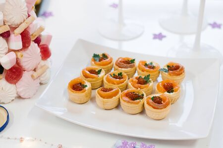 Tartlets with red fish salmon and red caviar on a Banquet or buffet table. Catering at the festival Фото со стока