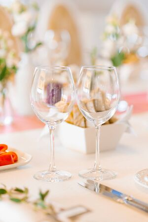 Two empty glass glasses in the wedding decor on a festive Banquet table Фото со стока