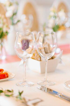 Zwei leere Glasgläser im Hochzeitsdekor auf einem festlichen Banketttisch