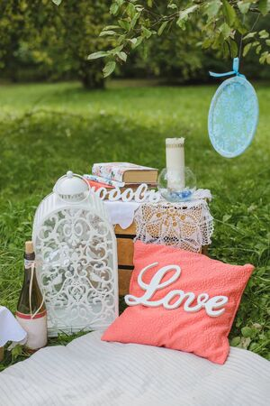 Romantic picnic decor for two: a pillow, a bottle of wine, a white lantern, books and candles on a blanket.Holiday Valentines day