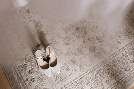 Gray womens open shoes on the carpet with a copy of the space. Morning of the bride and accessories of the female image