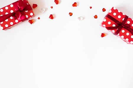 Border or banner for Valentines Day. Gifts with satin ribbon and bows, confetti, rhinestones, glass hearts on a light background. The Concept Of Valentines Day. Flat lay, top view, copy space