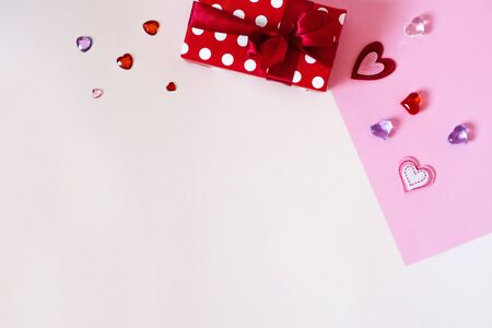 Gift box with a red satin bow and ribbon, red confetti hearts and gifts on a white and pink, multi-colored background. The concept of Valentines Day. The view from the top, flat lay.Copy space