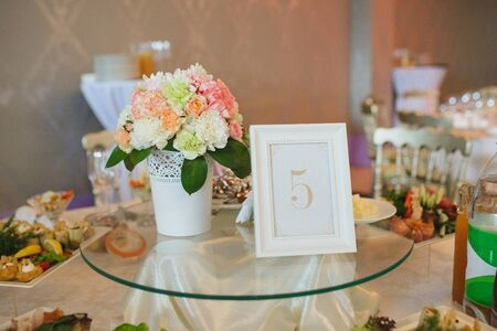 Decoration of the guest table with a sign 5 and flowers in a white vase at the wedding