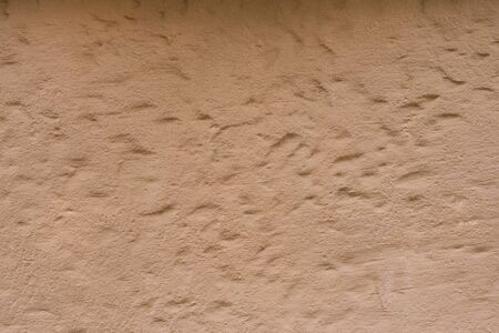 Beige or light brown plaster, rough wall texture, background for copying space