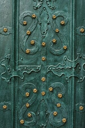 Lviv, Ukraine. October 2019. Elegant and beautiful patterns on the emerald - colored doors of the Dominican Cathedral