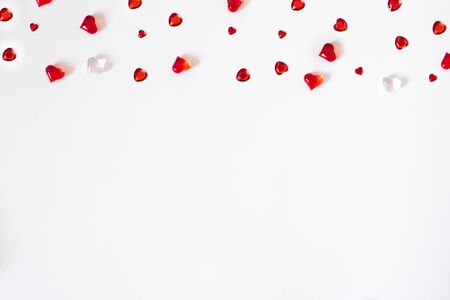 Confetti of red hearts. A scatter of a cornered border on a white Valentine background. Postcard with copying space for the day of Love Фото со стока