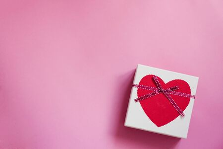 Festive background for Valentine's day with copying space. Gift box with a heart and a bow on a pink background