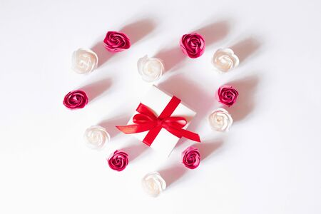 Heart of white and pink rose buds on a white background with a gift box. Valentines day card