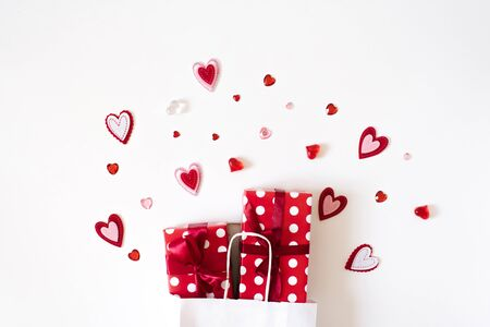 Top view of a colorful Valentine background made of a gift box and a variety of red hearts. Valentine's day card concept