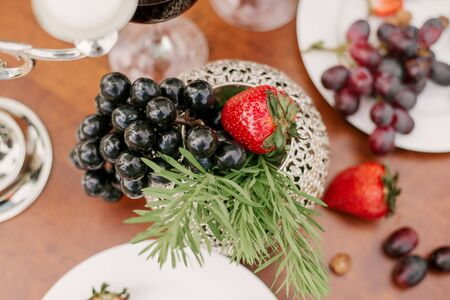 Fresh fruit, grapes and strawberries in the table setting or decoration on the holiday