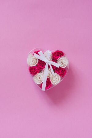 White and pink rose buds in a transparent heart-shaped box on a pink background. Valentines day card