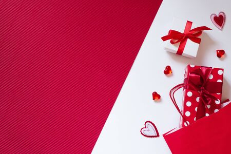 Shopping background with gift bags and sparkling decorative hearts on red and white background with copy space for your text. The background of Valentines day. Фото со стока