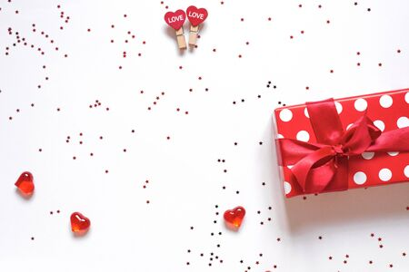 Top view colorful Valentine background made of gift box and red assorted hearts with confetti with copy space. Valentines day card concept