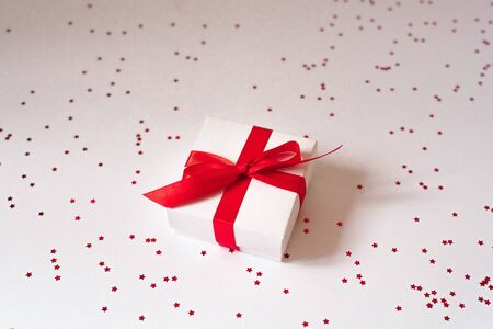 Valentines day composition, greeting card. Gift with a red ribbon and bow on a white background and a red confetti star. Фото со стока