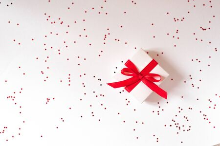 Christmas and Valentines day composition, greeting card. Gift with red ribbon and bow on white background background with red confetti star. The view from the top, flat lay