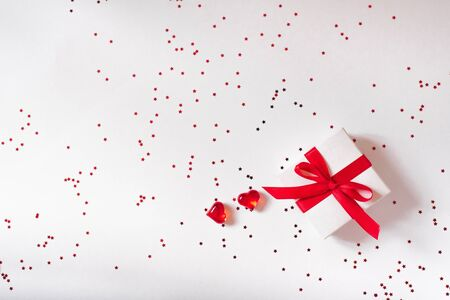 Valentines day composition, greeting card. A gift with a red ribbon and bow on a white background and two glass hearts with a red confetti star. Top view, flat la