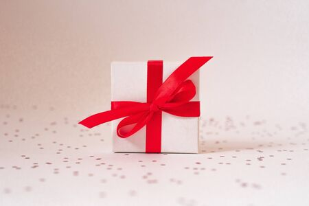 Gift white box with red satin ribbon and bow and stars on a white background. Valentines day, birthday, Christmas, New Year