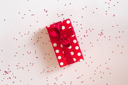 Gift white box with red satin ribbon and bow and stars on a white background. Valentines day, birthday, Christmas, New years Day Фото со стока