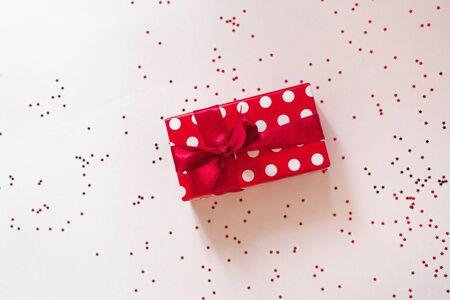 Gift box with red ribbon and glass heart on white background for Valentines Day.