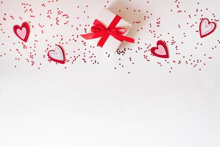 The background of Valentines day. Gift with a bow, hearts, confetti, on a white background. The concept of Valentines Day. Flat flat, top view, copy space