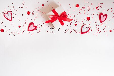 Valentines day card. Banner of a gift, hearts, confetti on a white background. The background of Valentines day. Flat lay, top view, copy space. Фото со стока