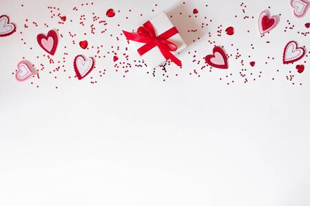 The background of Valentines day. Gift delivery service. Flat lay composition of a gift box with a red ribbon and felt hearts and confetti on a white background. Copy space. Фото со стока
