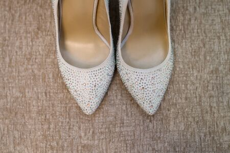 Womens grey shoes with rhinestones on a beige background. Accessories for the bride