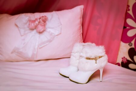 Womens white ankle boots with fur on a pink background. Accessories for the bride with space copying