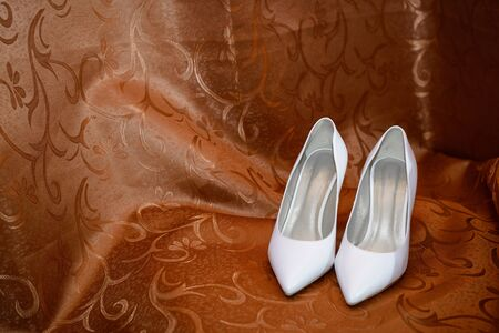 Women's white shoes on a red background. Accessories for the bride with space copying
