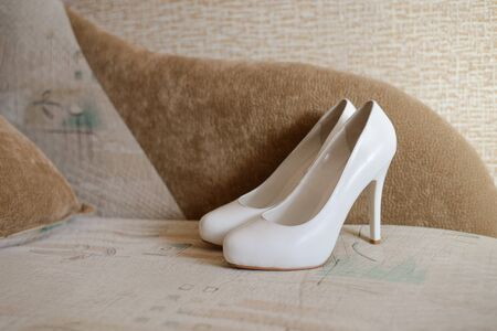 Womens white shoes on a beige background. Accessories for the bride