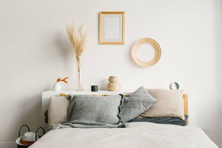 Bed in the bedroom in a Scandinavian minimalist natural style. Gray pillows on the bed. Decor above the bed and on the wall 免版税图像